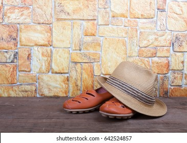 Straw hat and moccasins on a wooden table in front of a stone wall.