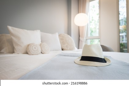 Straw hat on bed. ready for vacation