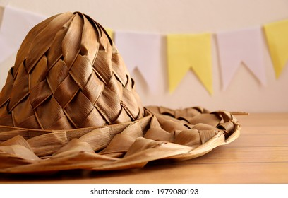 Straw hat on wooden table with banner flags party (Bandeirolas in portuguese) in the background. Concept of feast of Saint John in Brazil (Festa Junina no Brasil, in portuguese).