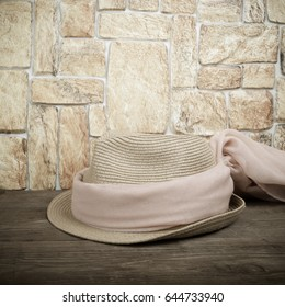 Straw hat and pink scarf on a wooden table in front of a stone wall. Toned.
