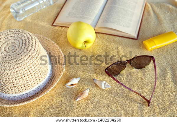 Straw hat, seashells, sunburn cream, sunglasses, apple, bottle with water and opened book on beige beach towel. Soft evening sunlight.