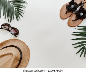 Straw hat, shoes, sunglasses and tropical leaf. Trendy travel background. Summer travel concept