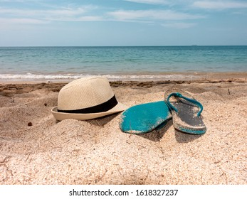 Straw hat and slippers on the white sand beach and sea and blue sky in the horizon