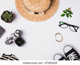 Straw hat, sneakers, vintage camera and other outfit on white background, top view