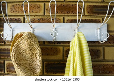 Straw hat and striped beach towel hanging on white hooks.