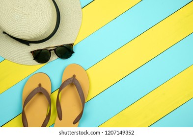 Straw hat, sun glasses, flip flops on yellow and light green wooden background.