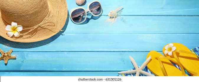 Straw hat, sun glasses and flip flops on blue wooden background