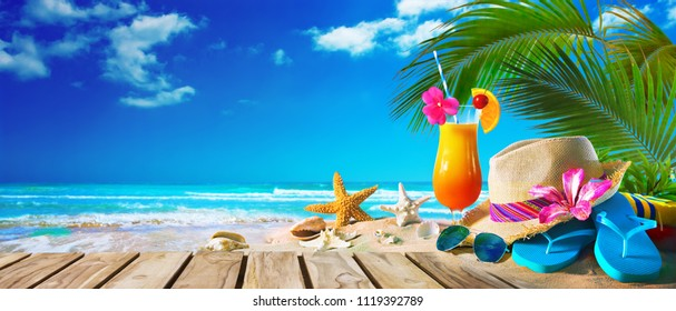 Straw hat with sunglasses and cocktail on sand beach. Summer Holidays concept