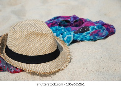 Straw hat, sunglasses and colorfull scarf on sandy tropical beach. Beach Accessories.Vacation concept.