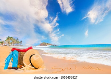 Straw hat, sunglasses, slippers and a bag on the golden sand of Sri Lanka's beach