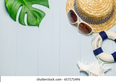 Straw hat with white sunglasses, lifebuoy and white seashell on blue wooden background with green leaves, Summer background