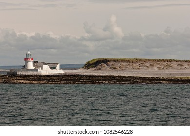 The Straw Island lighthouse at the entrance to Killeany Bay of Inishmore Island, view is south from within the bay from a ferry to Inishmaan.  Note nesting sea birds on the dune to the right.