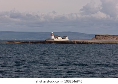 The Straw Island lighthouse at the entrance to Killeany Bay of Inishmore Island, the view is south from within the bay from a ferry en route to Inishmaan, the island rising in the distance.