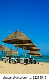 Straw kiosks on a beach in Aracaju, Sergipe, Brasil on a bright sunny day with blue skies - Imagem
