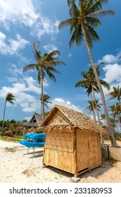 straw lodge on a sandy beach with high palm trees.