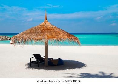 Straw parasol at white sand tropical beach