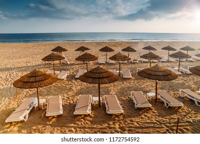 Straw parasols and beach loungers on the the sandy of Carcavelos beach in Lisbon, Portugal