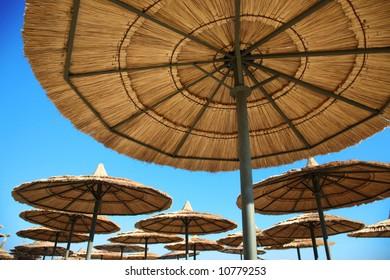 straw parasols on beach on blue sky background