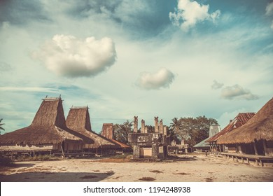 Straw roof houses, tombs. Traditional Sumba village. Authentic settlement on the cloudy sky background. The striking feature is that huts intermingle with tombs. Sumba island, Indonesia.