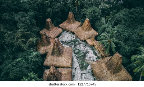 "Straw roof huts. Traditional Sumbanese village. Jungle. Cone shape authentic houses ""ratenggaro"" intermingle with tombs. Sumba island, Indonesia."