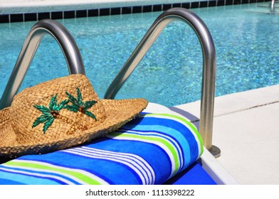 Straw sun hat and beach towel sitting on edge of swimming pool.