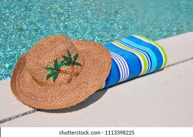 Straw sun hat and beach towel sitting on edge of swimming pool.