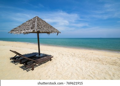 Straw sunshade and wooden sunbeds at a beautiful beach with white sand in Mangkuk Beach, Terengganu, Malaysia.