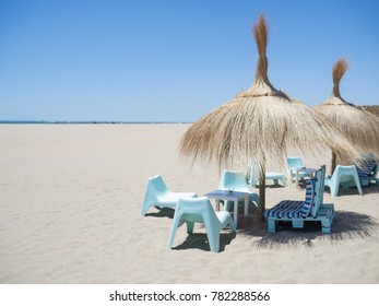 straw sunshades and blue chairs on a beach with golden sand in summer in andalucia, spain. Isla canela beach near ayamonte.