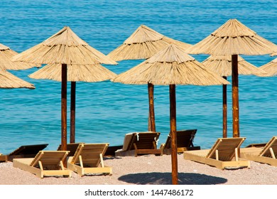 Straw sunshades and wooden sunbeds on an empty beach and turquoise water in the background