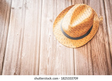 A straw trilby style summer hat on a rustic wood background with copy space