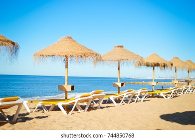 Straw umbrella on relaxing sea beach. Tropical sunny outdoors background.