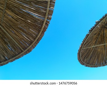 Straw umbrellas against a blue sky. Parasols. Summer season and holiday concept.