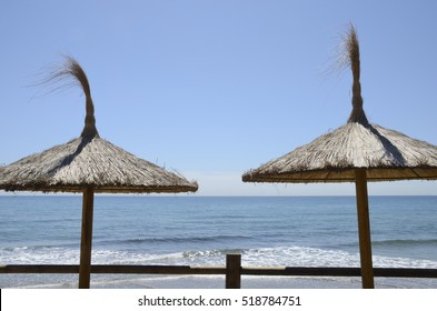 Straw umbrellas in the beach of  Marbella, a  city  in southern Spain, belonging to the province of Malaga, Andalusia, Spain