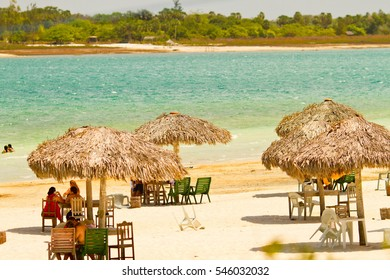 Straw umbrellas with chairs near of a lake known as Lagoa do Paraiso, at Jericoacoara, Brazil