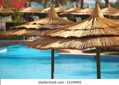 straw umbrellas on blue water