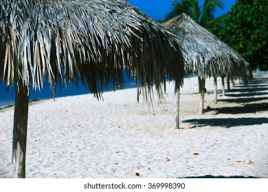 Straw umbrellas on Paradise beach in the Caribbean with white sand and palm trees