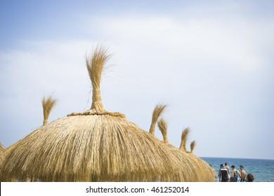 straw umbrellas on the shore of sea Marbella, Andalucia Spain