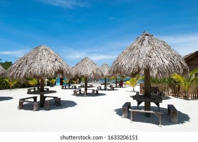 Straw umbrellas over wooden benches and tables on Mahogany Bay Beach on Roatan Island (Honduras).