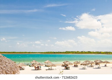 Straw umbrellas at the sky with clouds, near of a lake known as Lagoa do Paraiso, at Jericoacoara, Brazil