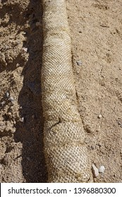 straw wattle staked to the ground for erosion control at a construction site