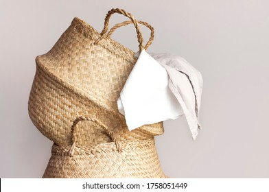 Straw wicker basket and white natural cotton fabric, towel on gray background. Fashionable bamboo basket stylish interior item eco design handmade. Decor of home. Natural eco materials, storage basket - Shutterstock ID 1758051449