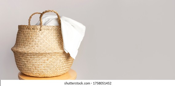 Straw wicker basket and white natural cotton fabric, towel on gray background. Fashionable bamboo basket stylish interior item eco design handmade. Decor of home. Natural eco materials, storage basket - Shutterstock ID 1758051452