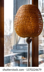Straw wicker lampshade on polished metal stand. Stylish interior lamp. Natural straw lattice texture with backlighting. Light beige grid patterned lamp. Geometric 3D shaped woven texture of floor lamp