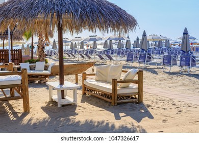 Straw and wooden sun umbrellas and chairs. Beach umbrellas and couches on blue sky and sea background on the beach of Italy. African style wooden beach furniture on beach of Milano Marittima, Adria