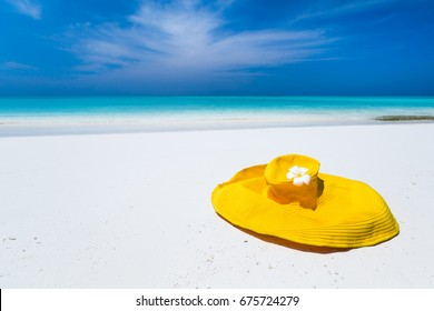 Straw yellow sunhat decorated frangipani flower on perfect wild sandy beach with turquoise sea view, nobody, travel destinations concept