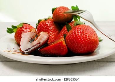 strawberries with balsamic vinegar over ceramic plate