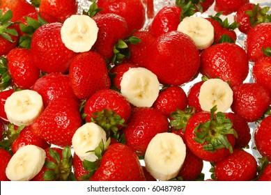 Strawberries and banana slices splashing in water