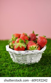 Strawberries in basket on grass.