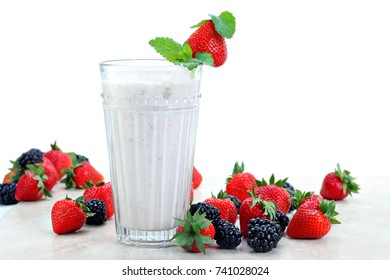 Strawberries and blackberries surround an fresh berry smoothie drink.  White background for copy space.