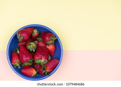 strawberries in blue bowl on pastel orange and yellow ground from above